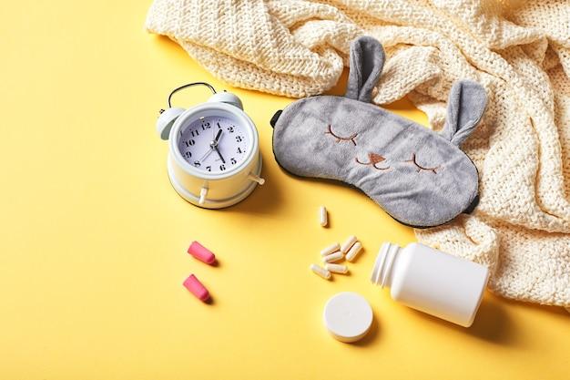 Masque de sommeil, réveil, bouchons d'oreille et pilules. concept créatif de sommeil de nuit saine. bonne nuit, hygiène du sommeil, insomnie