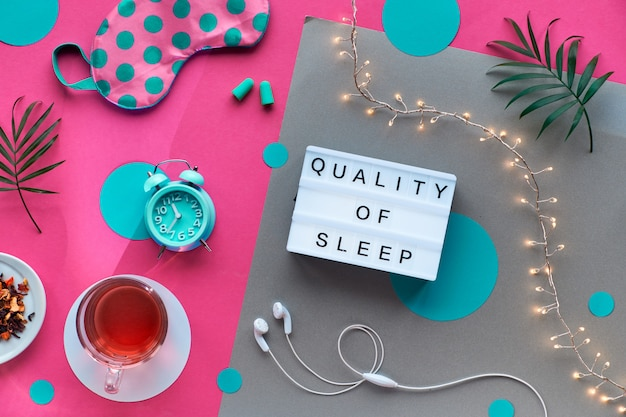 Masque de sommeil, réveil, écouteurs et bouchons d'oreille. remèdes calmants - pilules, capsules et thé. disposition plate, rose bicolore et papier kraft. texte