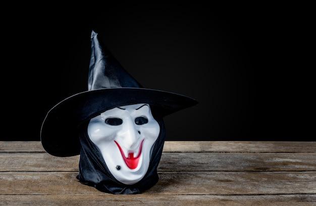 Masque de sorcière d'halloween sur plancher en bois, fond noir