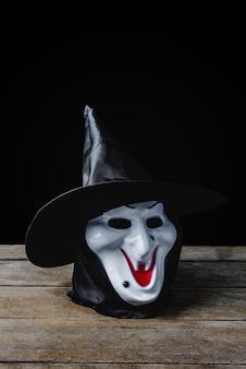 Masque de sorcière d'halloween sur plancher en bois et fond noir