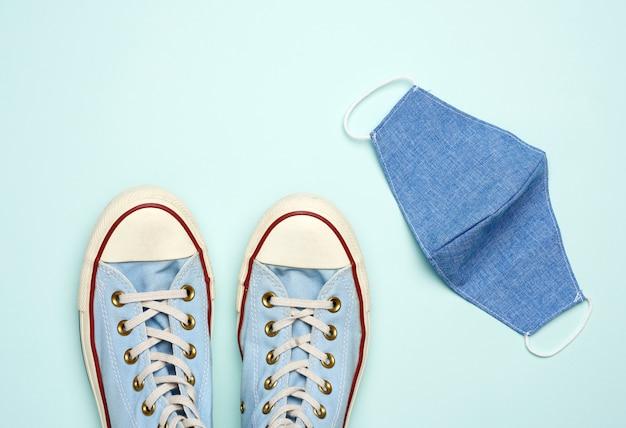 Masque textile réutilisable et baskets bleues sur une surface bleue