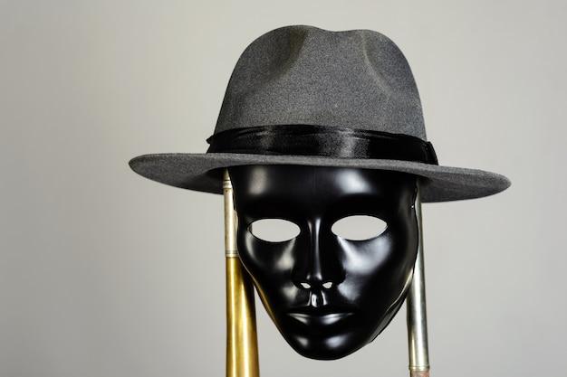 Masque de théâtre noir et chapeau accroché à un tuyau en laiton sur fond gris
