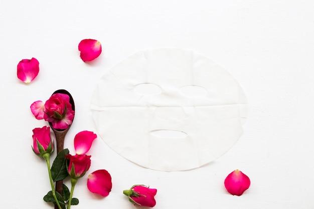 Masque en tissu naturel près de fleurs roses