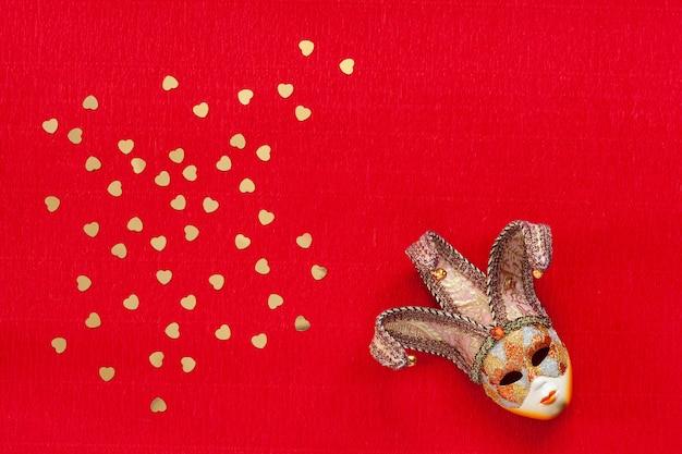 Masque vénitien avec des confettis de paillettes d'or en forme de coeur. vue de dessus, gros plan sur fond rouge