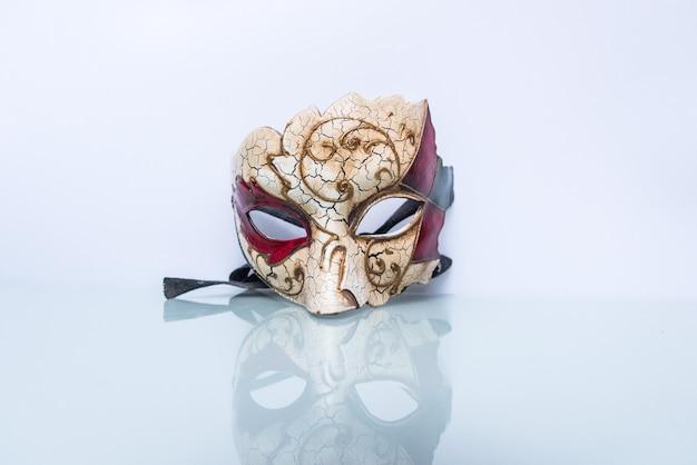 Masque vénitien sur fond blanc avec reflet dans la moitié inférieure