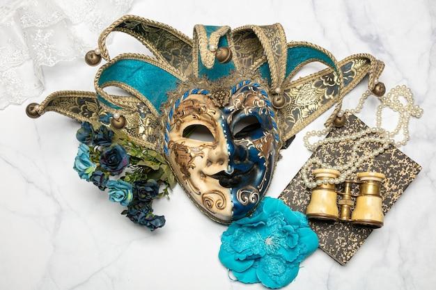 Masque vénitien avec un livre et des jumelles de théâtre sur une table en marbre