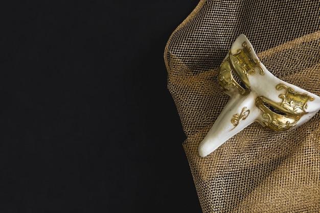 Masque vénitien avec un long nez sur un tissu doré