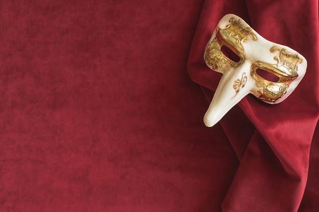 Masque vénitien avec un long nez sur un tissu rouge