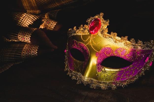 Masque vénitien d'or et rose sur un fond sombre