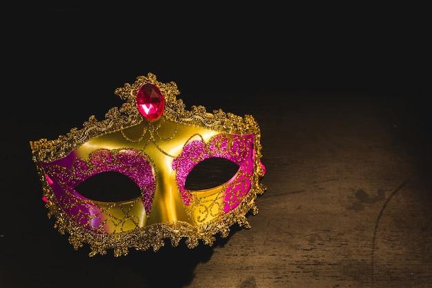 Masque vénitien d'or sur une table en bois