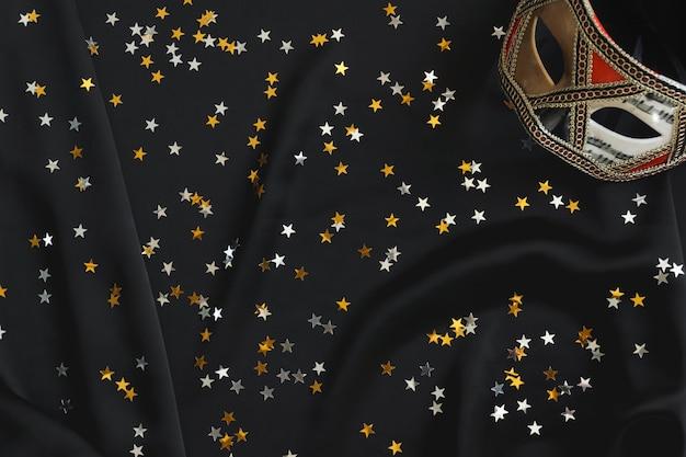 Masque vénitien sur un tissu noir avec des confettis étoiles