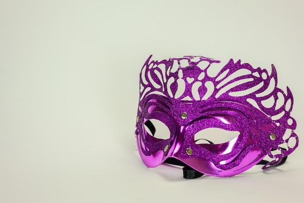 Masque vénitien violet sur fond blanc pour le carnaval de bal masqué.