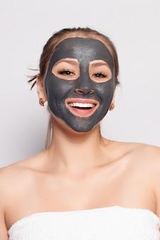 Masque de visage de femme. portrait de belle fille enlevant le masque de peeling noir cosmétique de la peau du visage. gros plan d'une jeune femme séduisante avec un maquillage naturel et un masque cosmétique sur le visage. haute résolution