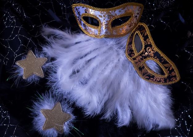 Masques de carnaval blanc et noir avec des étoiles de plumes et des étincelles