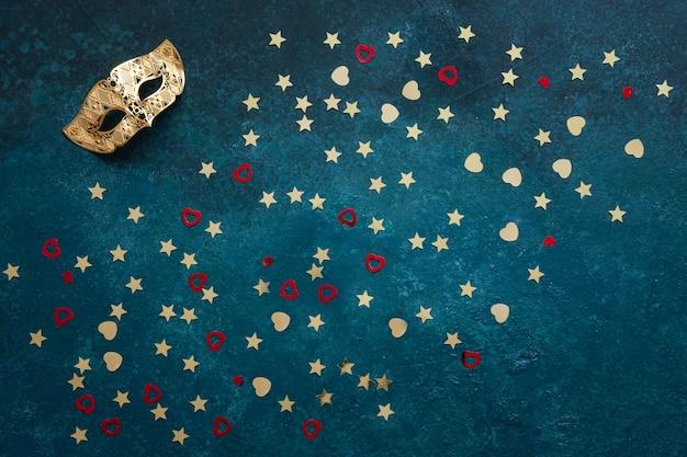 Masques de carnaval et confettis de paillettes d'or. vue de dessus, gros plan sur fond bleu