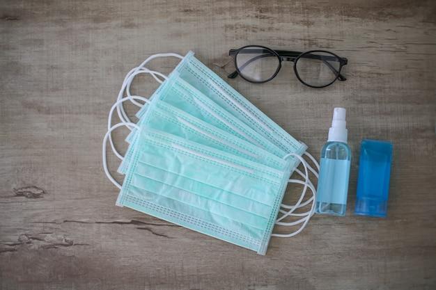 Masques chirurgicaux, lunettes et bouteille de gel désinfectant pour les mains