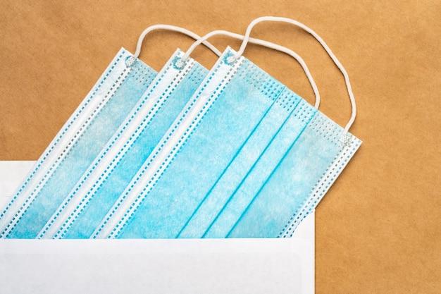 Masques chirurgicaux médicaux bleus dans une enveloppe postale blanche sur fond de papier kraft jaune. mise à plat, vue rapprochée. concept de prise en charge des personnes aimées à distance, forcé pendant la distance sociale pandémique