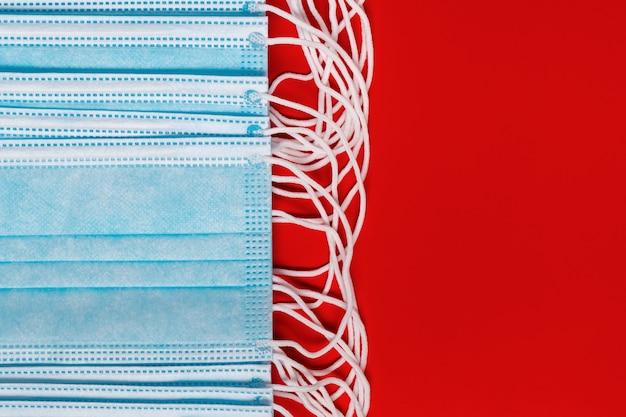 Masques chirurgicaux et médicaux pour coronavirus sur fond rouge. vue rapprochée d'un bandage facial respiratoire avec des sangles d'oreille en caoutchouc. espace de copie, protection du concept, 2019-ncov, prévention des virus.