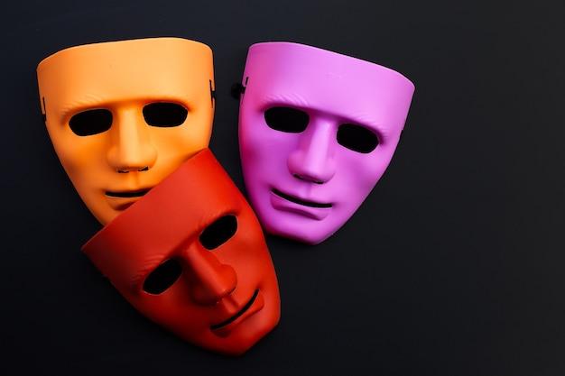 Masques faciaux sur une surface sombre.