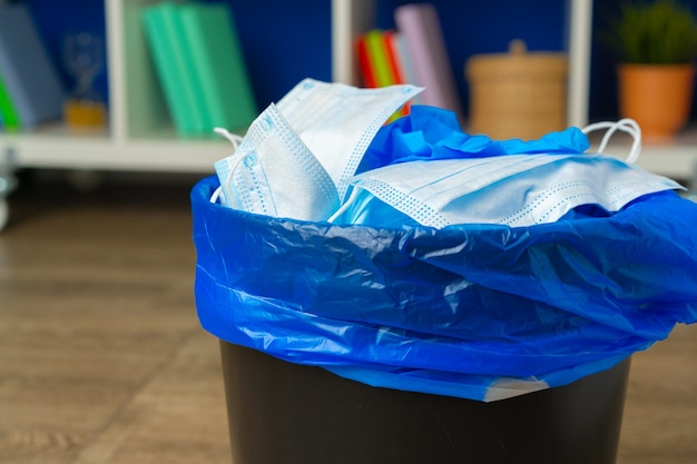 Masques infectieux usagés et gant médical dans la poubelle