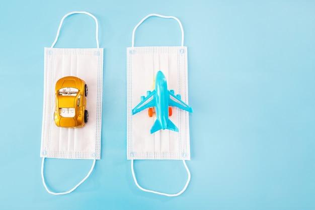 Masques médicaux, avion jouet et auto sur fond bleu. espace de copie. place pour votre texte.