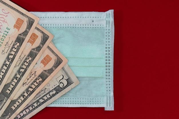 Masques médicaux et billets en dollars comme symbole de l'augmentation des prix pour la protection des voies respiratoires contre les virus. copiez l'espace.