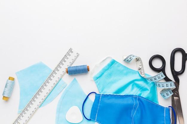 Masques médicaux avec des ciseaux et du fil