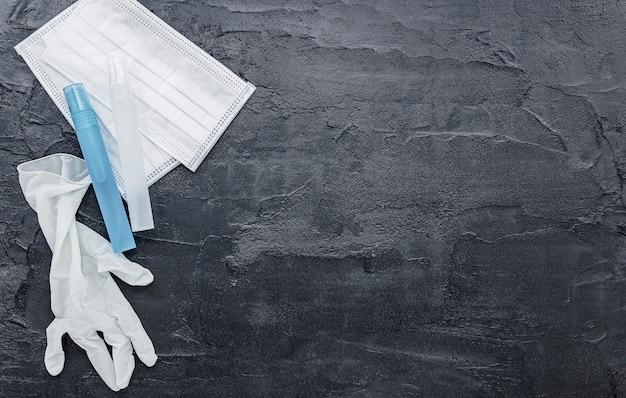 Masques médicaux et gants de protection sur fond de béton foncé