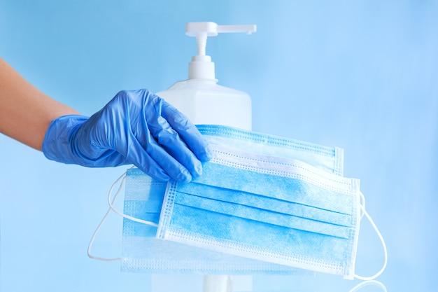 Masques médicaux, masque protecteur jetable chirurgical dans la main du médecin avec des gants bleus. gel désinfectant pour alcool en bouteille. coronavirus covid 19 hygiène de prévention des virus sur fond bleu.
