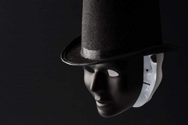 Masques noir et blanc portant chapeau noir