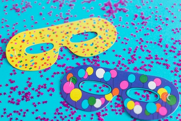 Masques en papier sur les confettis