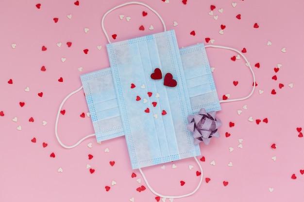Masques de protection médicale contre le coronavirus dans le concept de la saint-valentin avec de petits coeurs rouges sur rose