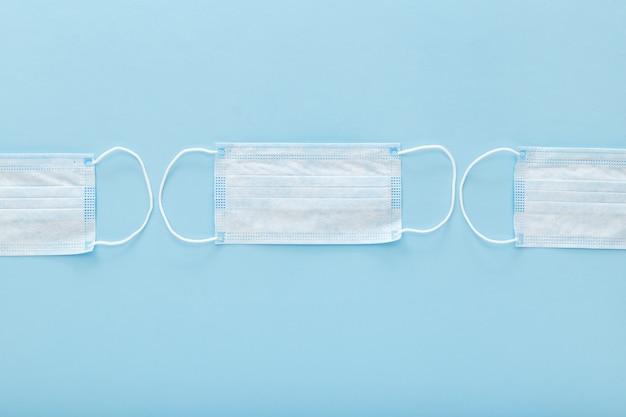Masques de protection médicale sur fond bleu. un masque facial chirurgical jetable couvre la bouche et le nez. concept de soins de santé