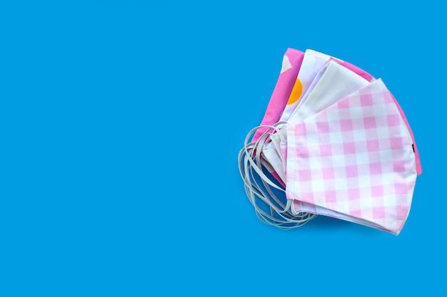 Masques en tissu coloré à la main sur fond bleu.