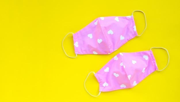 Masques en tissu rose et coeur faits à la main sur fond jaune.