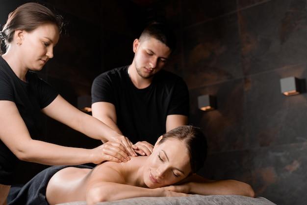 Massage à 4 mains au spa. deux masseurs font un massage relaxant à quatre mains avec de l'huile pour fille. relaxation. thérapie manuelle.