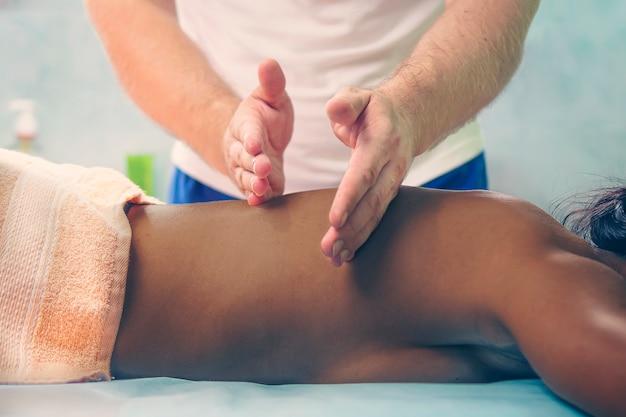 Massage agrandi. femme afro-américaine se faire masser. un physiothérapeute fait un massage du dos pour une femme noire.