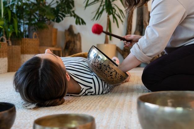 Massage aux bols chantants tibétains pour les loisirs une femme utilise une thérapie sonore pour la récupération du stress à la maison
