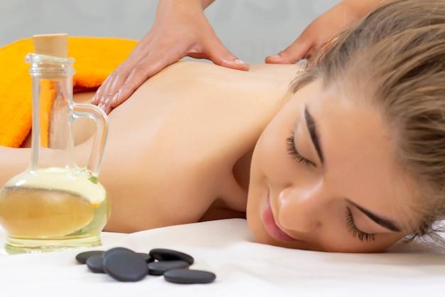 Massage aux pierres chaudes du spa. jolie belle fille allongée sur un lit de massage dans un salon spa. concept d'aromathérapie et de soins de beauté spa