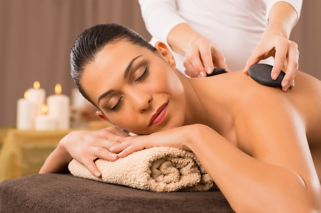 Massage aux pierres chaudes d'une jeune femme