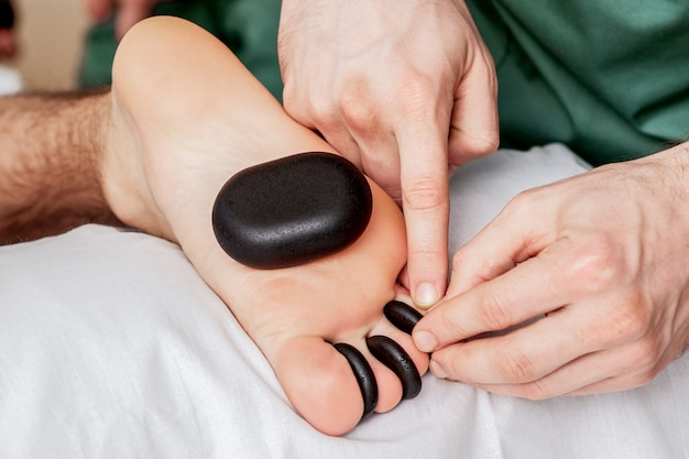 Massage aux pierres chaudes sur les orteils.