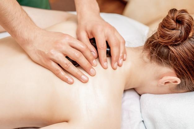 Massage aux pierres sur le dos de la femme