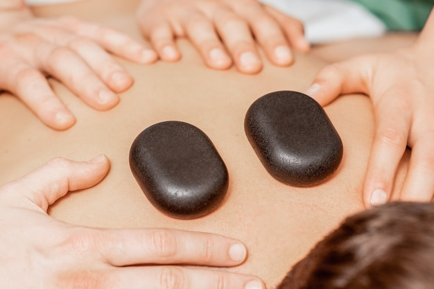 Massage aux pierres sur le dos de l'homme