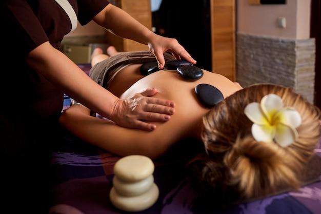 Massage aux pierres du dos pour femme au centre de beauté.