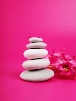 Massage aux pierres de spa, traitement relaxant, cairn de pierre sur fond blanc gris rayé, tour de cinq pierres, pierres d'équilibre simples, simplicité, harmonie et équilibre, rock zen