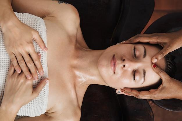 Massage ayurvédique du visage avec de l'huile sur la table en bois