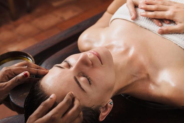 Massage Ayurvédique Du Visage Avec De L'huile Sur La Table En Bois Photo Premium