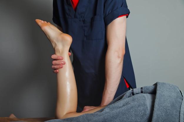 Massage bien-être sportif dans la salle médicale de la salle de fitness. le masseur fait des exercices de massage. massage thérapeutique régénérant du corps sportif