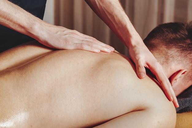 Massage bien-être sportif dans la salle médicale de la salle de fitness. le masseur fait des exercices de massage
