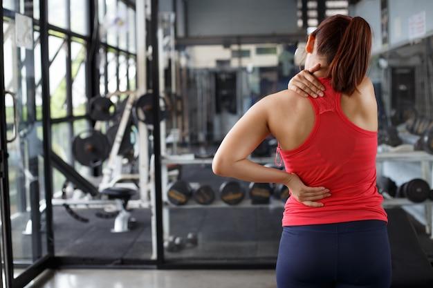Massage du corps féminin dans le fond de la salle de gym. concepts de soins de santé et d'exercice.